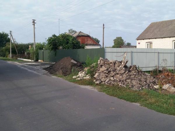 Село Острівок, вулиця Шкільна. Будівельне сміття та усілякий непотріб лежить на обочині, а діти ходять по дорозі
